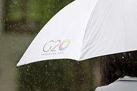 """29.11.2018, Argentinien, Buenos Aires: Eine Frau geht im Regen mit einem Schirm, bedruckt mit dem G20-Logo, in das Internationale Pressezentrum. Vom 30.11. bis 01.12.2018 findet in Buenos Aires der G20-Gipfel statt. Die """"Gruppe der 20"""" vereint die stärksten Industrienationen und aufstrebenden Volkswirtschaften. Foto: Ralf Hirschberger/dpa +++ dpa-Bildfunk +++"""