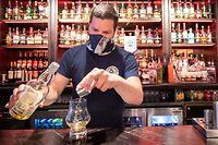 ARCHIV - 15.07.2020, Großbritannien, Edinburgh: Barkeeper Dejah Hajdukovic serviert einen Whisky im Pub «The Piper's Rest». Pubs, Cafés und Restaurants dürfen nach den Plänen der Regionalregierungen in beiden britischen Landesteilen wieder öffnen. Foto: Jane Barlow/PA Wire/dpa +++ dpa-Bildfunk +++