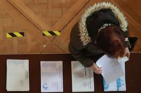 A voter looks at election materiel at a polling station in Le Touquet, northern France on March 15, 2020, during the first round of the mayoral elections. - Officials have been told to disinfect voting booths and ballot boxes throughout the day, and sinks and hand gels will be made available. People will be urged to get in and out quickly to avoid lines, and floor markings will be laid out to ensure they stay one metre (3.3 feet) from one another. Authorities have already eased proxy voting rules for people at risk or infected with coronavirus and ordered to confine themselves to their homes, as well as for people in retirement homes. People can also come with their own pens for marking ballots. (Photo by Ludovic Marin / AFP)
