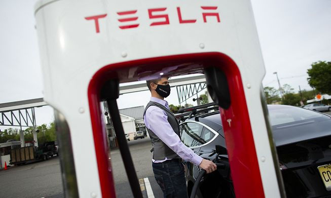 Ben Rich charges his Tesla vehicle at a super charging station in the US state of New Jersey on 6 May