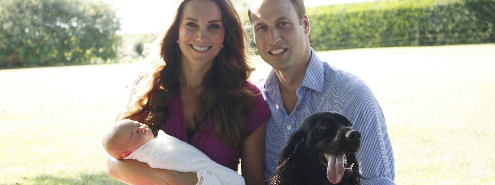 Das Foto, das vom Vater von Herzogin Kate Anfang August 2013 aufgenommen wurde, zeigt William und Kate mit ihrem Sohn Prinz George im Garten des Hauses der Familie Middleton in Bucklebury, umgeben von Retriever Tilly und Cockerspaniel Lupo.