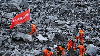 """Rescue workers search for survivors at the site of a landslide that occurred in Xinmo Village, Mao County, Sichuan province, China June 24, 2017. The writing on the flag reads: """"Chengdu Fire Departmant Rescue Team"""". REUTERS/Stringer ATTENTION EDITORS - THIS IMAGE WAS PROVIDED BY A THIRD PARTY. CHINA OUT. NO COMMERCIAL OR EDITORIAL SALES IN CHINA."""
