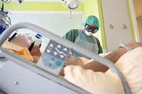 A healthcare worker wearing personal protective equipment (PPE) treats a Covid-19 patient in an intensive care unit (ICU) at the University Hospital Tulln in Vienna, Austria on November 27, 2020. (Photo by HELMUT FOHRINGER / APA / AFP) / Austria OUT