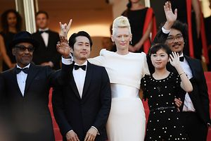 (From L) Danish-born actor Giancarlo Esposito, US-South Korean actor Steven Yeun, British actress Tilda Swinton, South Korean actress Ahn Seo-hyun and South Korean director Bong Joon-ho wave as they arrive on May 19, 2017 for the screening of the film 'Okja' at the 70th edition of the Cannes Film Festival in Cannes, southern France.  / AFP PHOTO / Anne-Christine POUJOULAT