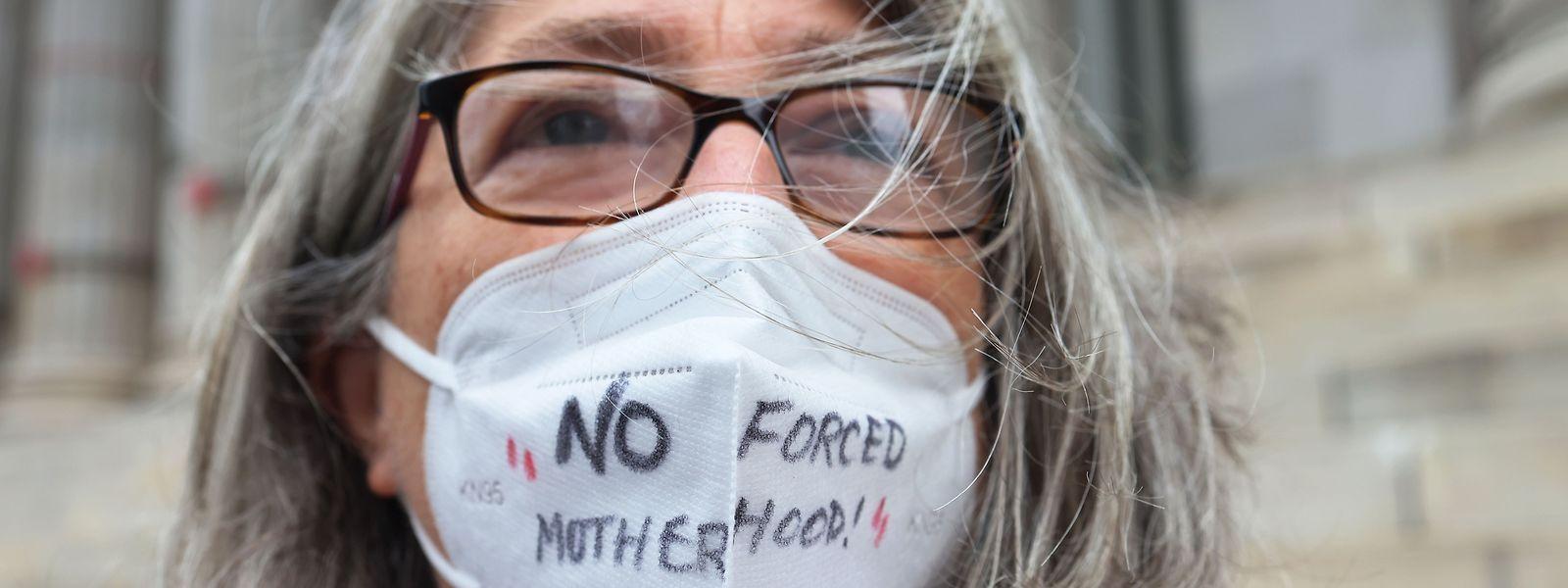 """Eine Verfechterin des Rechts auf Abtreibung trägt eine Maske mit der Aufschrift: """"No forced motherhood"""" (auf deutsch """"Keine erzwungene Mutterschaft"""")."""