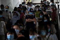 Passengers wearing face masks walk through a subway station in Beijing on June 15, 2020. (Photo by Noel Celis / AFP)