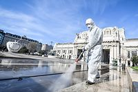 13.03.2020, Italien, Mailand: Ein Arbeiter im Schutzanzug desinfiziert die Piazza Duca d'Aosta vor dem Bahnhof Milano Centrale. Foto: Claudio Furlan/LaPresse via ZUMA Press/dpa +++ dpa-Bildfunk +++