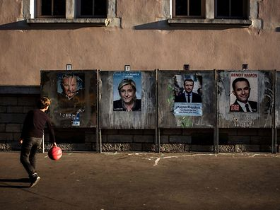 A boy plays basketball by campaign posters for the French presidential election on official billboards on April 21, 2017 in Lyon, ahead of the first round of the French presidential election which will take place on April 23. / AFP PHOTO / JEFF PACHOUD