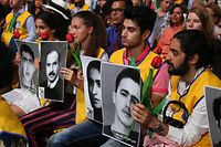 """People hold pictures of relatives killed by the Mohllas regime, during """"Free Iran 2018 - the Alternative"""" event on June 30, 2018 in Villepinte, north of Paris during the Iranian resistance national council (CNRI) annual meeting.  / AFP PHOTO / Zakaria ABDELKAFI"""