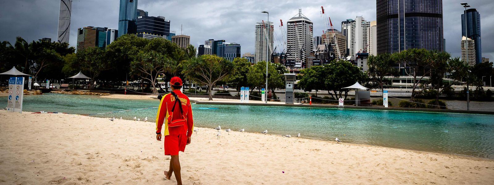 """Nadador-salvador numa praia deserta em Brisbane, que decretou novo lockdown nos últimos dias. Todo o país está em alerta """"muito elevado"""" para as novas variantes e mais contagiosas da covid-19."""