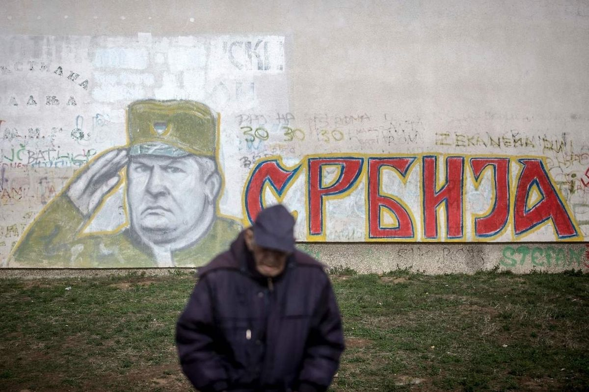 """A man stands in front of a graffiti depicting former Bosnian Serb commander Ratko Mladic and reading """"Serbia"""" written in Cyrillic, painted on a wall in Belgrade."""