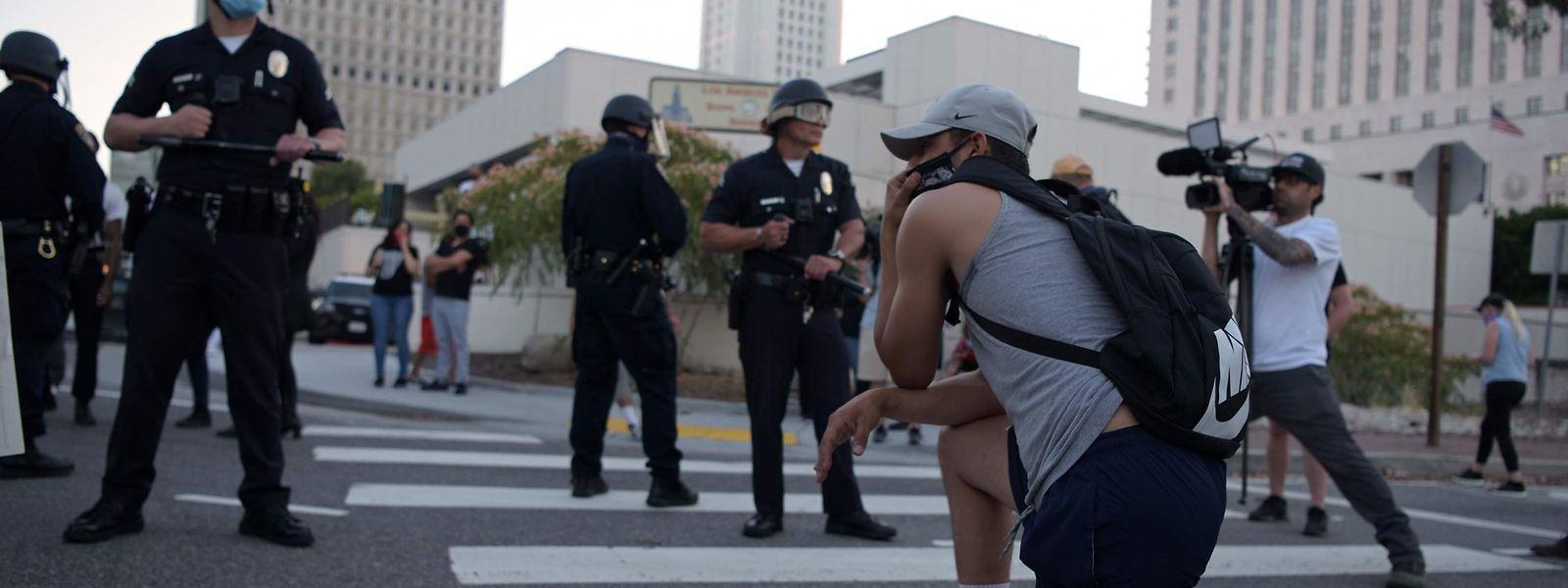 Demonstranten knien in Anlehnung an die Geste von Colin Kaepernick vor der Polizei.