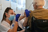 A nurse administers a dose of the Pfizer-BioNtech coronavirus disease (Covid-19) vaccine to an elderly person on January 4, 2020 in the Bellevue gerontology center in Montpellier in the south of France. - French president faced on January 4, 2020 growing pressure to accelerate France's Covid-19 vaccination drive which has seen just a few hundred people receive the jab. (Photo by Pascal GUYOT / AFP)