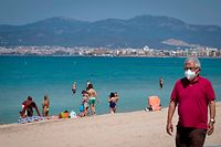 People sunbathe at Palma Beach in Palma de Mallorca on May 31, 2020. - Spain's government today said it would seek parliament's approval to extend the state of emergency by another fortnight, until June 21, what would allow to keep on restricting people's mobility during deconfinement process. (Photo by JAIME REINA / AFP)