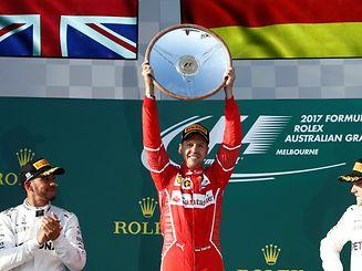 Ferrari driver Sebastian Vettel of Germany (C) celebrates alongside Mercedes driver Lewis Hamilton of Britain (L) and team mate Valtteri Bottas of Finland