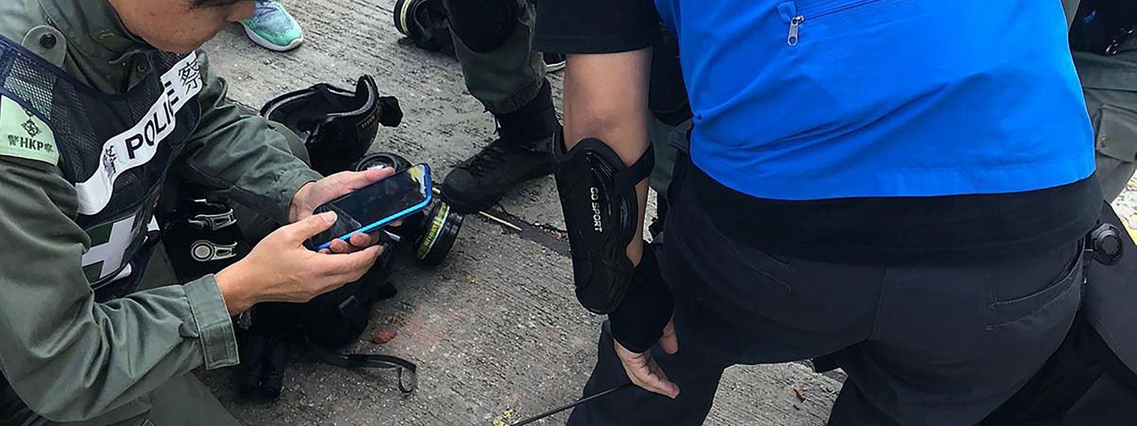 Kollegen untersuchen einen Polizisten in Hongkong, der von einem Pfeil getroffen wurde.