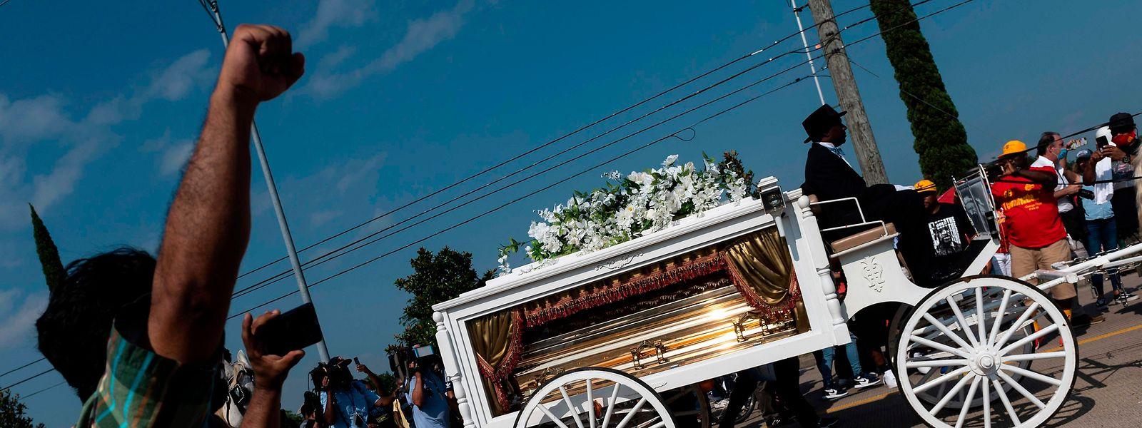 """Ein Mann hebt die Faust, während der Sarg von George Floyd von einer weißen Pferdekutsche zu seiner letzten Ruhestätte auf dem Friedhof """"Houston Memorial Gardens"""" in Pearland gebracht wird."""