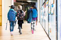 Girls (8-9) walking together through school corridor