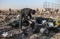08.01.2020, Iran, Shahedshahr: Retter durchsuchen an der Absturzstelle die Trümmer. Eine ukrainische Passagiermaschine ist in der Nähe des Imam-Chomeini-Flughafens der iranischen Hauptstadt Teheran abgestürzt. Nach Angaben der Hilfsorganisation iranischer Halbmond kamen alle Insassen ums Leben. Foto: Mohammadreza Abbasi/dpa +++ dpa-Bildfunk +++