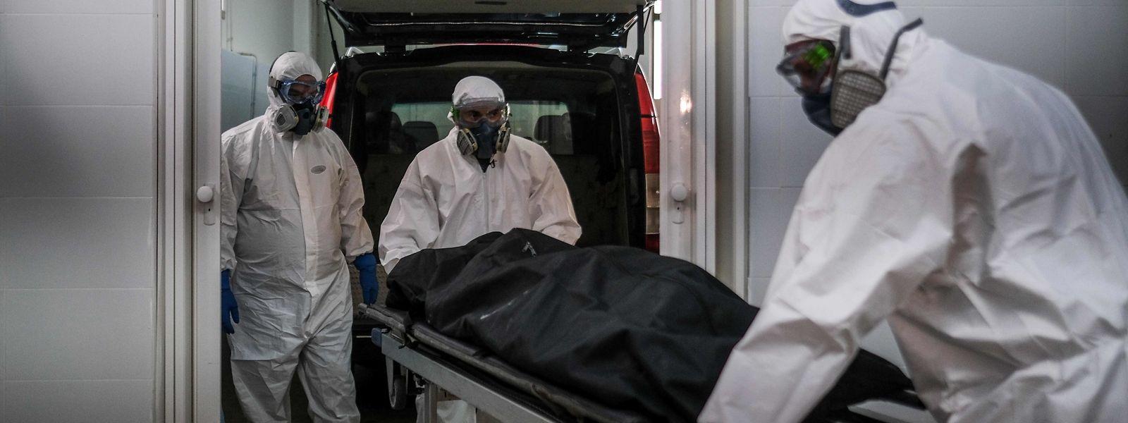 Im portugiesischen Amadora bei Lissabon tragen Bestatter die Leiche eines Covid-19-Opfers weg.