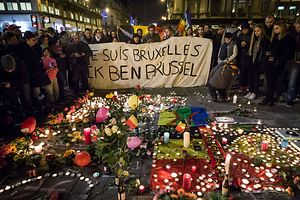 "People hold a banner reading in French and Flamish ""I AM BRUSSELS"" as they gather around floral tributes, candles, belgian flags and notes in front of the Bourse of Brussels on March 22, 2016  in tribute to the victims of Brussels following triple bomb attacks in the Belgian capital that killed about 35 people and left more than 200 people wounded.  Belgium launched a huge manhunt on March 22 after a series of bombings claimed by the Islamic State group ripped through Brussels airport and a metro train, killing around 35 people in the latest attack to bring carnage to the heart of Europe.  / AFP PHOTO / BELGA AND Belga / Aurore Belot / Belgium OUT"