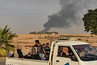 "TOPSHOT - Civilians ride a pickup truck as smoke billows following Turkish bombardment on Syria's northeastern town of Ras al-Ain in the Hasakeh province along the Turkish border on October 9, 2019. - Turkey launched an assault on Kurdish forces in northern Syria with air strikes and explosions reported along the border. President Recep Tayyip Erdogan announced the start of the attack on Twitter, labelling it ""Operation Peace Spring"". (Photo by Delil SOULEIMAN / AFP)"