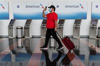 (FILES) In this file photo taken on May 12, 2020, a passenger walks past empty American Airlines check-in terminals at Ronald Reagan Washington National Airport in Arlington, Virginia. - American Airlines is notifying 25,000 workers that they could be furloughed beginning October 1, although the number of layoffs may be minimized through voluntary programs, executives said on July 15, 2020. The major US carrier will have more than 20,000 more workers on payroll than needed due to a profound downturn in business caused by the coronavirus pandemic, Chief Executive Doug Parker and President Robert Isom said in a memo to employees. (Photo by ANDREW CABALLERO-REYNOLDS / AFP)