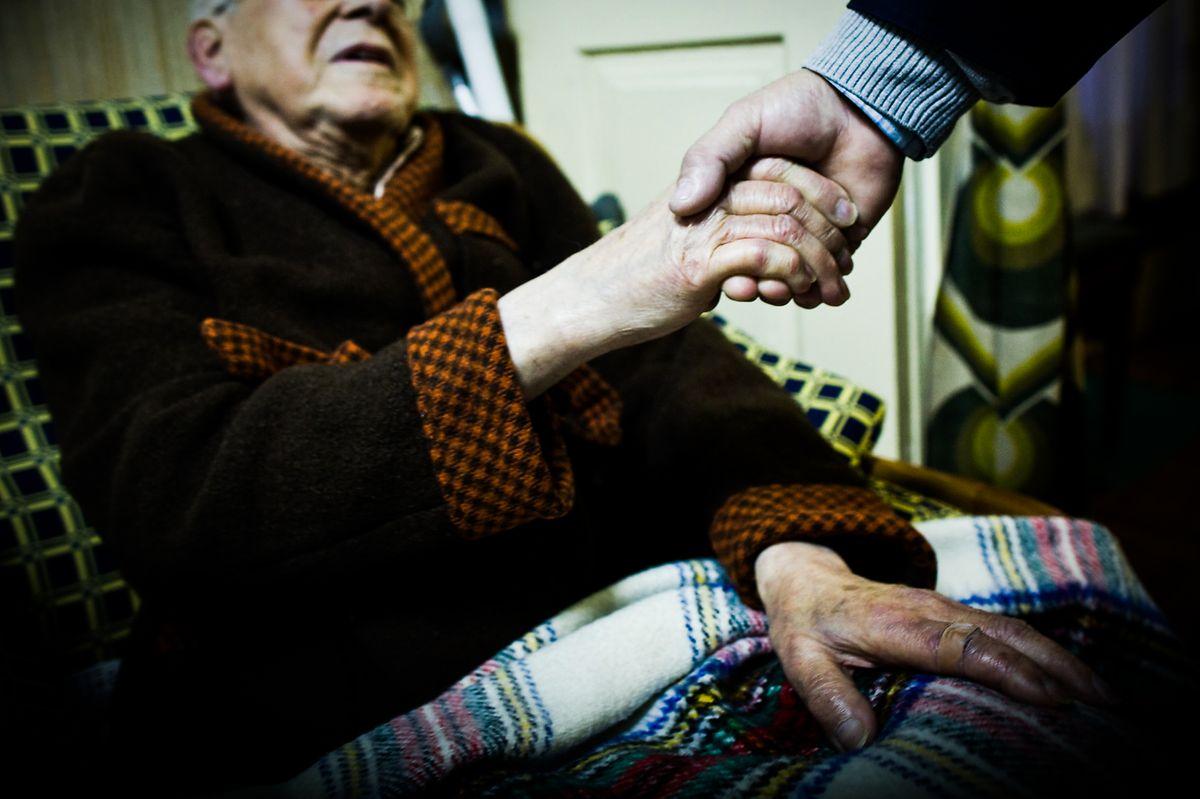 Um voluntário cumprimenta um idoso num lar de terceira idade. O toque da humanidade é agora um risco.