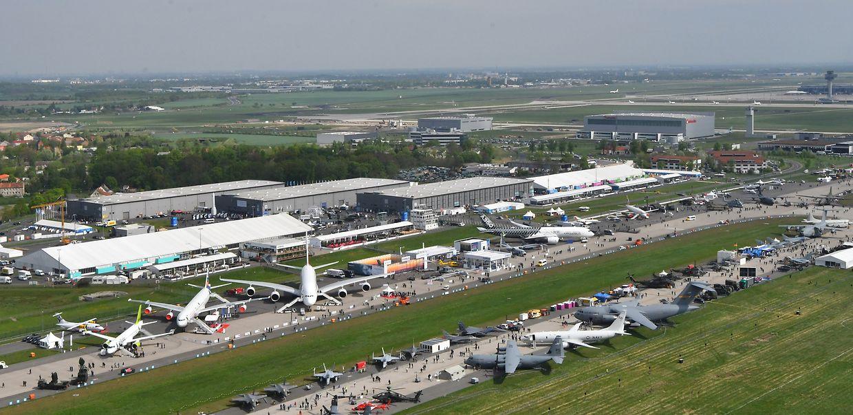 Fachbesucher laufen in Schönefeld über das Gelände der Internationalen Luft- und Raumfahrtausstellung (ILA).