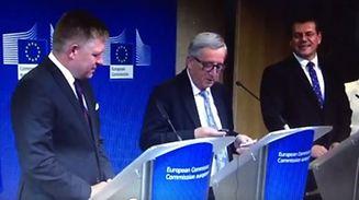 Jean-Claude Juncker wird bei einer Pressekonferenz durch einen Anruf von Angela Merkel abgelenkt.