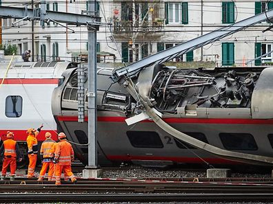 Police officers and workers inspect the site of a train crash