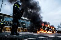 TOPSHOT - A car has been set on fire in front of the train station, on January 24, 2021 in Eindhoven, after a rally by several hundreds of people against the corona policy. (Photo by ROB ENGELAAR / various sources / AFP) / Netherlands OUT