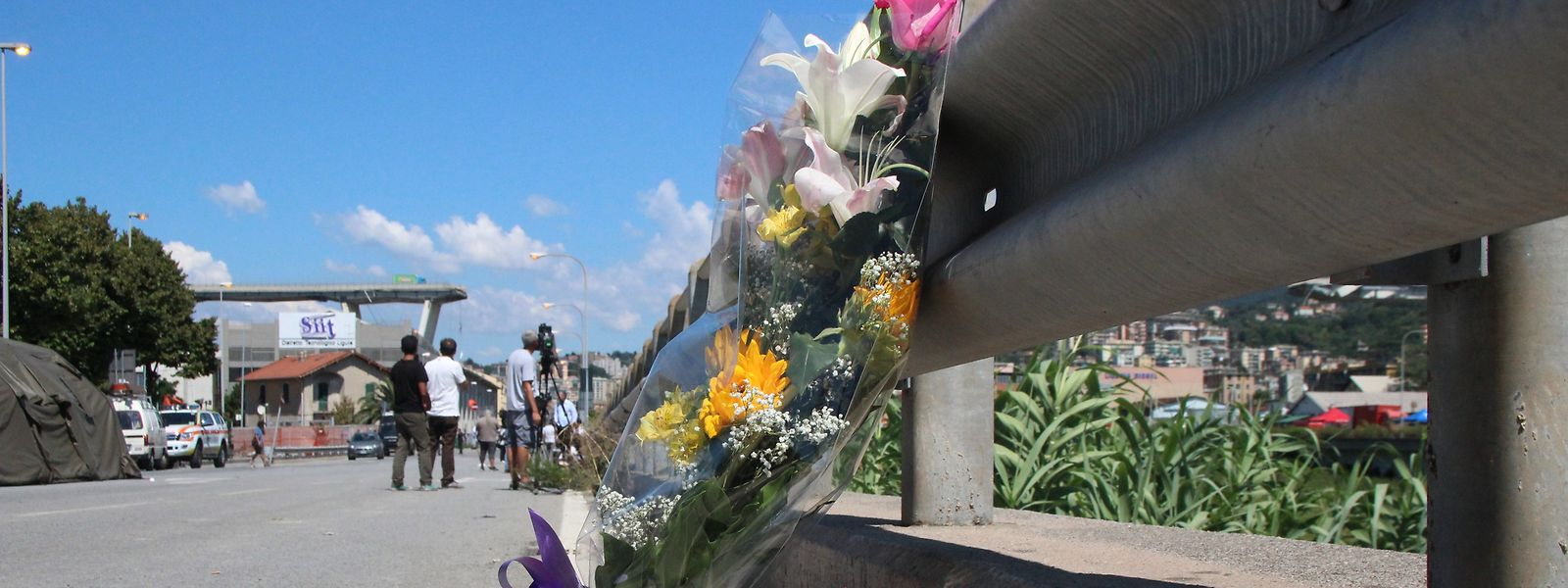 Ein Blumenstrauss steht in einiger Entfernung von der eingestürzten Brücke.