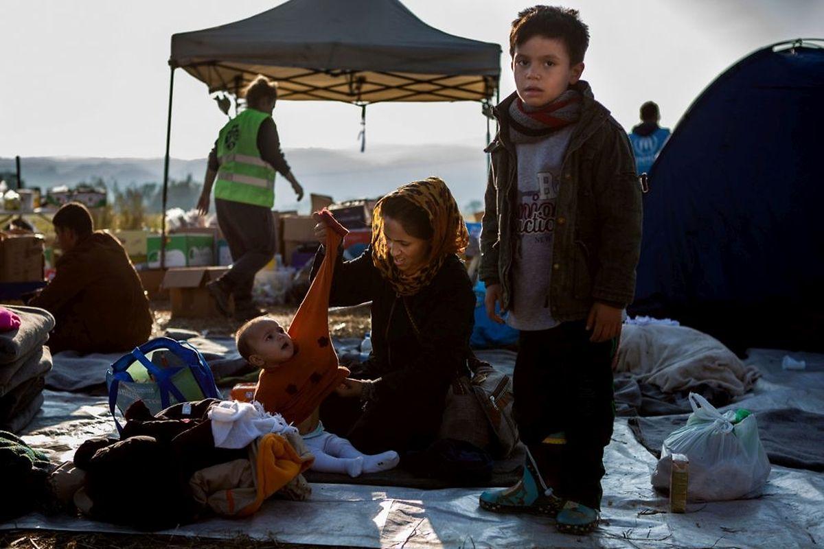 Une femme s'occupe de ses enfants à l'écart, après avoir réussi à sortir du camp.Son bébé est malade et a été pris en charge par un médecin militaire.