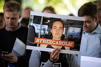 """TOPSHOT - Demonstrators hold a banner reading """"Free Carola"""" during a vigil on July 2, 2019 in Cologne, western Germany, for Carola Rackete, a German captain of a migrant rescue ship, who was arrested in Italy. - Sea-Watch 3 skipper Carola Rackete was arrested at the weekend after a two-week standoff at sea and faces up to 10 years in jail if convicted. (Photo by Federico Gambarini / dpa / AFP) / Germany OUT"""