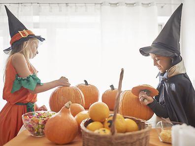 Little siblings to work on Halloween pumpkins