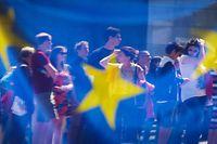 ARCHIV - 17.05.2014, Belgien, Brüssel: Menschen spiegeln sich in einem Fenster mit einer europäischen Flagge im Europäischen Parlament. Vom 23.05. bis 26. Mai wählen die Bürger von 28 EU-Staaten ein neues Parlament. Foto: Olivier Hoslet/EPA/dpa +++ dpa-Bildfunk +++