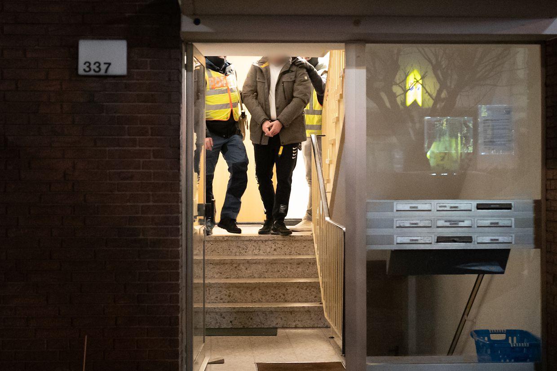 Beamte der Polizei führen einen vorläufig festgenommenen Mann aus einem Mehrfamilienhaus.