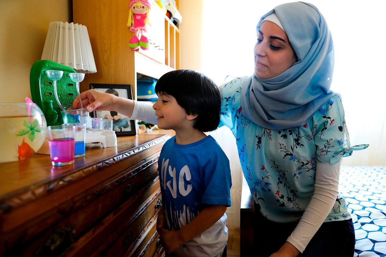 Hassan Mubaied, filho de Maher Mubaied (ausente na foto) e Safa Mubaied (E) brinca no seu quarto. Os sonhos de Maher e de Safa ficaram adiados com a guerra na Síria, mas reencontraram a paz em Portugal, onde residem há dois anos ao abrigo de um programa de acolhimento de refugiados. É no primeiro andar de um prédio da freguesia de Barcarena, no concelho de Oeiras, que Maher Mubaied, de 25 anos, reside com a esposa Safa, da mesma idade, e Hassan, o filho de ambos, com quatro anos, desde setembro de 2017. Chegaram a Portugal ao abrigo de um programa europeu de recolocação de refugiados, depois terem passado pela Turquia e pela Grécia, e já no nosso país contaram com o apoio do Centro Social e Paroquial de Barcarena. Barcarena, 17 de junho de 2018. ( ACOMPANHA TEXTO DO DIA 19 DE JUNHO DE 2019). JOÃO RELVAS/LUSA