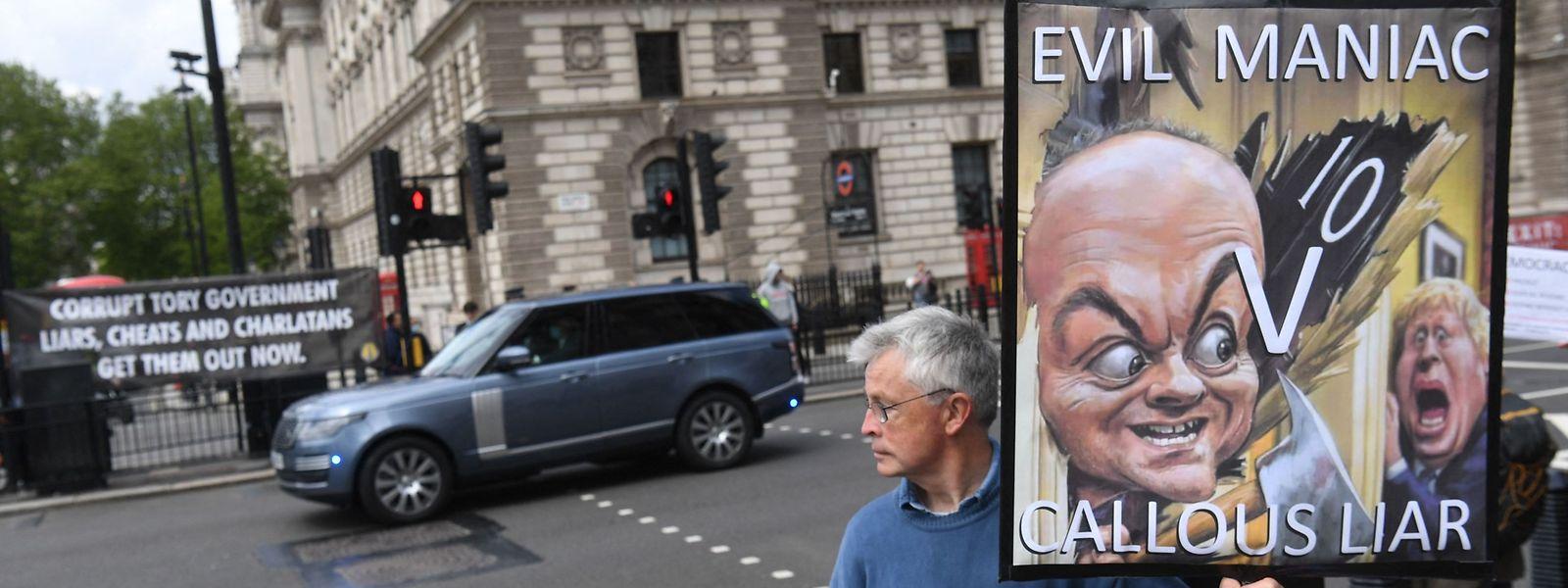 Ein Demonstrant mit einem Plakat, das den Machtkampf zwischen Dominic Cummings und Boris Johnson illustriert.