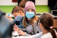 21.10.2020, Hessen, Frankfurt/Main: Mit Mundschutzmasken sitzen Schülerinnen und Schüler der fünften Klasse eines Gymnasiums in Frankfurt im Unterricht, ein Mädchen trägt eine Mütze. Neben dem obligatorischen Tragen von Masken gehört das regelmässige Lüften der Klassenräume zum Hygienekonzept an den hessischen Schulen. Foto: Boris Roessler/dpa +++ dpa-Bildfunk +++