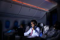 Businessman working at laptop on night airplane