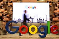 (FILES) In this file photo taken on January 22, 2019 a technician passes by a logo of US internet search giant Google during the opening day of a new Berlin office of Google in Berlin. - Google parent Alphabet reported a rare drop in revenue and profit on July 30, 2020, in a quarterly update that nonetheless topped market expectations. (Photo by Tobias SCHWARZ / AFP)