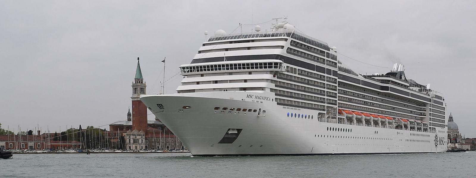 Ein Kreuzfahrtschiff fährt an der Lagunenstadt Venedig von einem Schlepper gezogen vorbei.