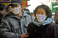 Chinese, wearing masks, walk down the streets of Beijing Tuesday, Dec. 30, 2003. The World Health Organization sent a four-member team to southern China on Monday to help investigate a suspected SARS case, while state media said none of the 81 people quarantined after having contact with the patient has shown symptoms. (AP Photo/Ng Han Guan)