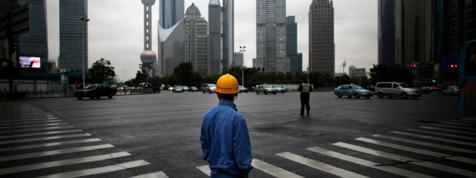Un ouvrier les mains dans les poches à proximité de Shanghai. L'économie mondiale devrait connaître un sérieux ralentissement au cours des prochains mois.