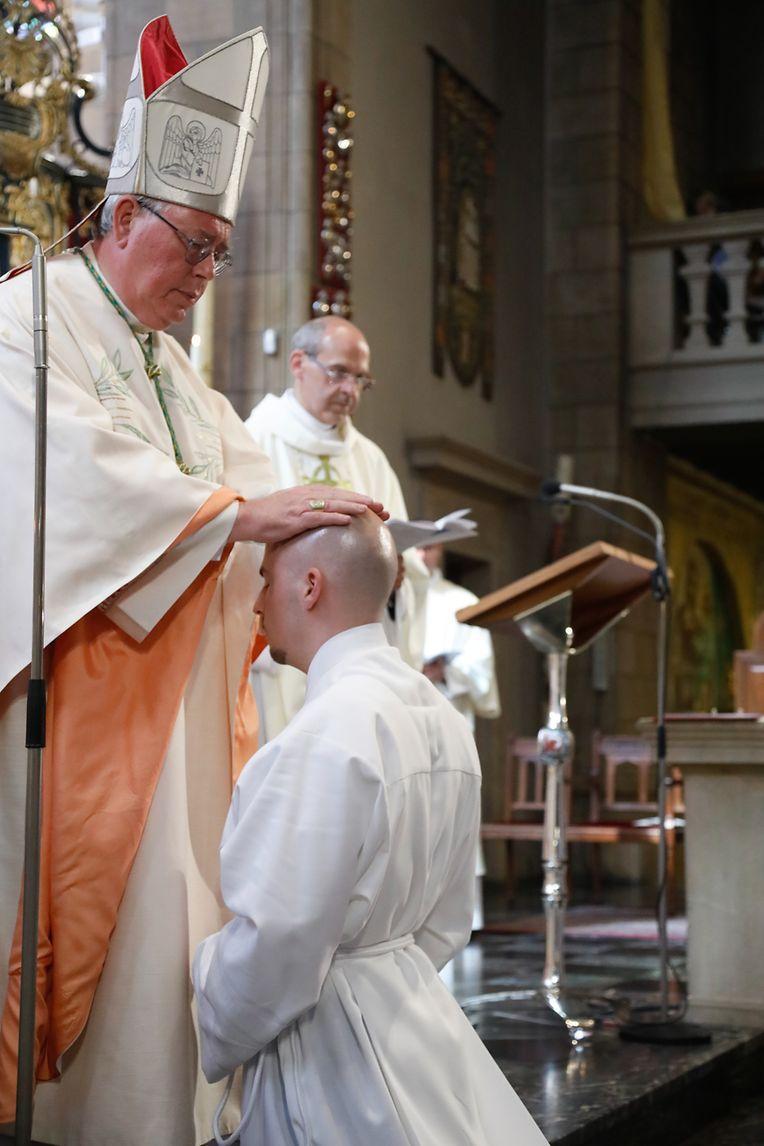Erzbischof Jean-Claude Hollerich legt Vincent De Smet die Hand auf – und überträgt ihm somit das Amt des Diakons.