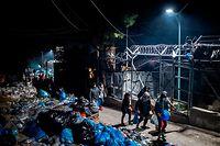 """ARCHIV - 22.01.2020, Griechenland, Lesbos: Migranten gehen an Müllsäcken vorbei in einem provisorischen Lager neben dem Lager in Moria. Die Lager auf den Inseln Lesbos, Samos, Chios, Kos und Leros sind völlig überfüllt, und die Atmosphäre ist entsprechend verzweifelt und aufgeheizt. (zu dpa """"Migrationskrise in der Ägäis: Insulaner blockieren Zufahrtsstraßen"""" am 24.02.2020) Foto: Angelos Tzortzinis/dpa +++ dpa-Bildfunk +++"""