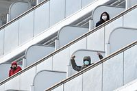 TOPSHOT - A passenger aboard the Diamond Princess cruise ship waves to the media upon arriving at Yokohama port on February 6, 2020. - Ten more people on a cruise ship off Japan have tested positive for the new coronavirus, local media said, raising the number of infections detected on the boat to 20. (Photo by Kazuhiro NOGI / AFP)