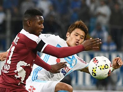 Metz' French forward Opa N'Guette (L) vies for the ball with Olympique de Marseille's Japanese defender Hiroki Sakai during the French L1 football match Olympique of Marseille (OM) versus Metz at the Velodrome stadium in Marseille on October 16, 2016.  / AFP PHOTO / BORIS HORVAT
